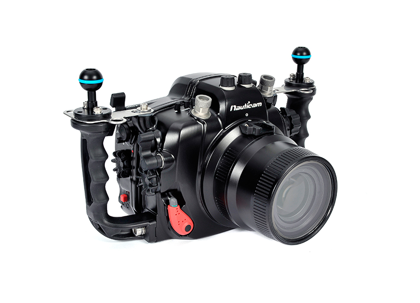 Nauticam Подводный бокс для Canon 6DNA-6D   -  Подводный бокс Nauticam для фотокамеры Canon 6D. Nauticam в последние годы инициировал множество технических прорывов в производстве подводных боксов, и они стали теперь уже стандартными опциями в модели NA-6D.  Запатентованный мульти-джойстик, расположенный в области досягаемости большого пальца правой руки,  позволяет осуществлять управление по 8 направлениям, при этом по прежнему доступное командное колесо перенесено на правую сторону бокса. Никакой другой производитель не делает доступ к этим важнейшим органам управления столь эргономичным. Запатентованная система закрывающих механизмов Nauticam получила всеобщее признание в мире. Углубленные в корпус защелки оборудованы красными кнопками безопасности. Такой конструктив замков бокса уменьшает общие габариты и требует минимального усилия для открывания и закрывания бокса. Смена портов никогда не была такой легкой и быстрой до появления запатентованной системы фиксации портов Nauticam. Не нужно поворачивать порт, не нужно прилагать усилия, невозможен перекос, нужно просто вставить и зафиксировать. Объективы также легко менять не вынимая камеру из бокса, для этого выведена специальная кнопка на передней панели корпуса. Легкие рукоятки бокса выполненные двухкопонентным литьем, имеют анатомическую форму, обрезинены, что предотвращает скольжение мокрых рук и делает захват максимально удобным. Nauticam быстро стал символом эргономики подводных боксов. Модель NA-6D является также отличным примером, на котором понятно почему это так. Положение каждого органа управления тщательно выверялось, каждая кнопка, рычаг и переключатель рассматривались не с точки зрения облегчения разработки бокса в производстве, а исключительно с точки зрения удобства съемки для пользователя. Стоит только взглянуть на конструкцию и дизайн правой стороны бокса. Ключевые органы управления самой съемкой также выведены таким образом, чтобы быть легко доступными не снимая руки с рукоятки бокса, с минималь