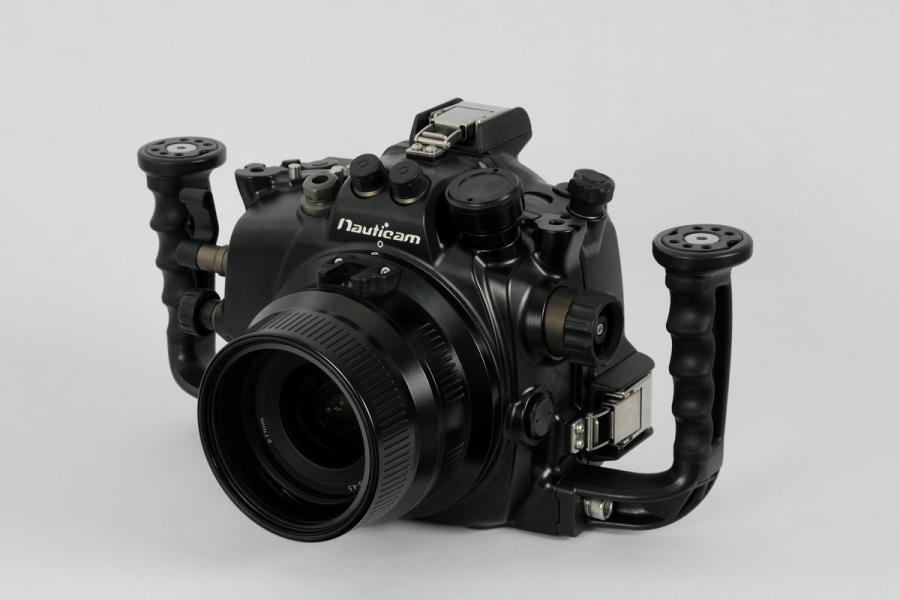 """Nauticam Подводный бокс для Canon 7DNA-7D – подводный бокс для цифровой зеркальной фотокамеры Canon 7D.  Если вы будете сравнивать бокс NA-7D с предыдущими боксами Nauticam, то обратите внимание, что расположение органов управления изменено таким образом чтобы ими оперировать не снимая рук с рукояток бокса. Новинкой является набор клавиш напоминающих """"пианино"""" на задней стенке бокса. Они заметно облегчают доступ к некоторым функциям камеры. Дайверам теперь нет необходимости выравнивать положение переключателей on/off, still/video  на камере перед закрытием бокса, подпружиненные механизмы сделают это самостоятельно. Бокс в стандартной поставке оснащен штатным  х0,66-видоискателем и оптическими разъемами синхронизации (имеется также гнездо для опциональной установки электрического разъема). Конструкция бокса специально поддерживает функции видеосъемки. Компания Nauticam делает на этом акцент. Большой и удобный рычаг управления видеосъемкой установлен под правой рукой рядом с рукояткой. На боксе имеется 4 штатных посадочных места для установки осветителей разного типа. Как правило, это 2 фонаря видеосвета и 2 фотовспышки.<br>"""